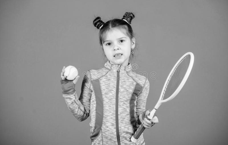 Sport upbringing. Small cutie likes tennis. Little baby sporty costume play tennis game. Teach me how to play tennis. Girl cute child double bun hairstyle stock image