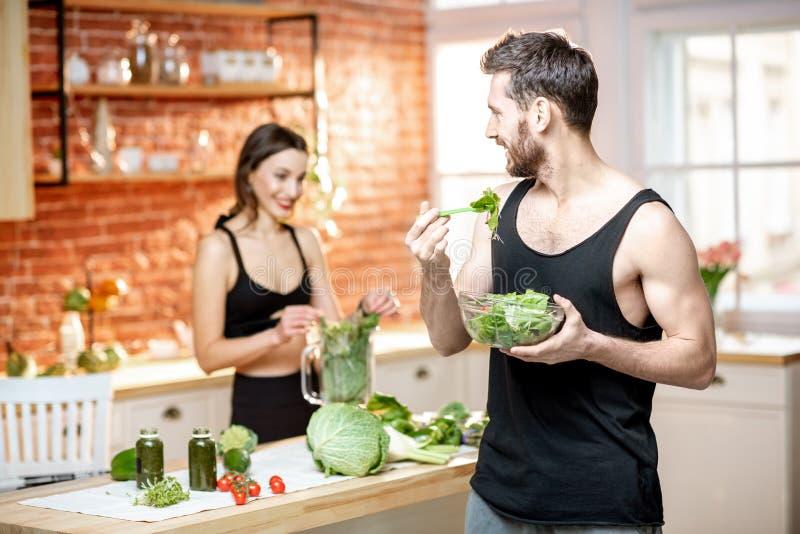 Sport verbindet das Essen der gesunden vegetarischen Nahrung auf der Küche stockfoto