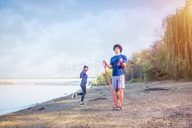 Sport verbindet den Ausbildungsdraußenmann, der mit Widerstand ausarbeitet stockbild