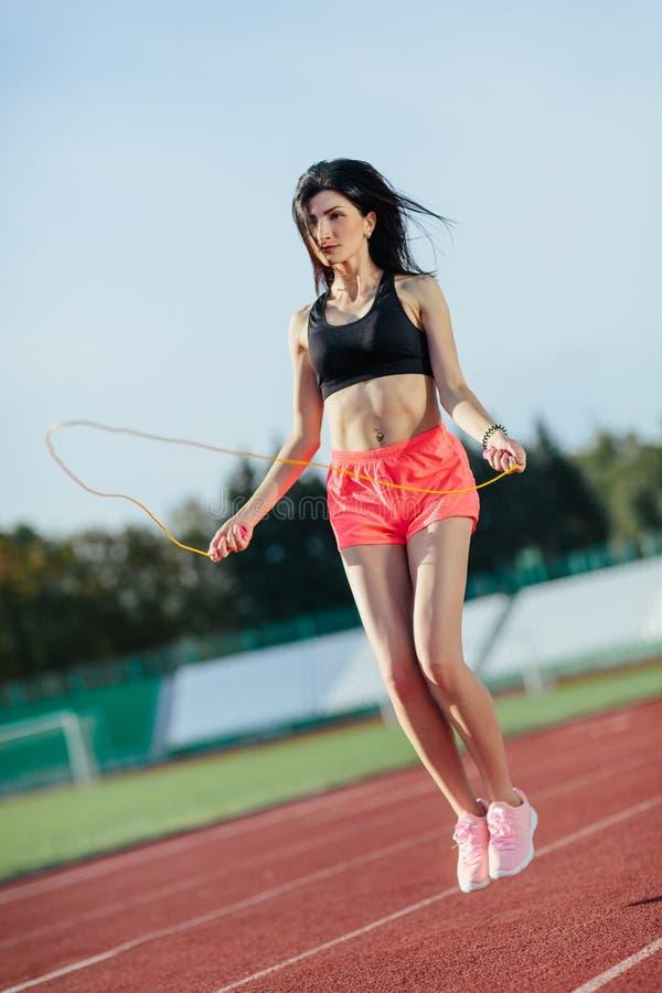 Sport ?vningar utomhus Brunettkvinnan i svart överkant och steg kortslutningar som hoppar på överhopprep på stadion Sportig flick arkivfoto