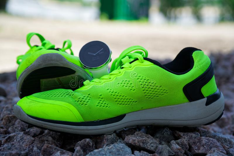 Sport watch for crossfit and triathlon on the green running shoes. Smart watch for tracking daily activity and strength training. royalty free stock photos