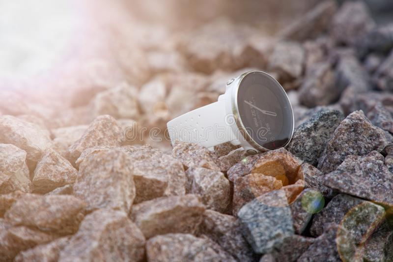 Sport watch for triathlon on the granite gravel. Smart watch for tracking daily activity and strength training. Sun beam lights royalty free stock photos