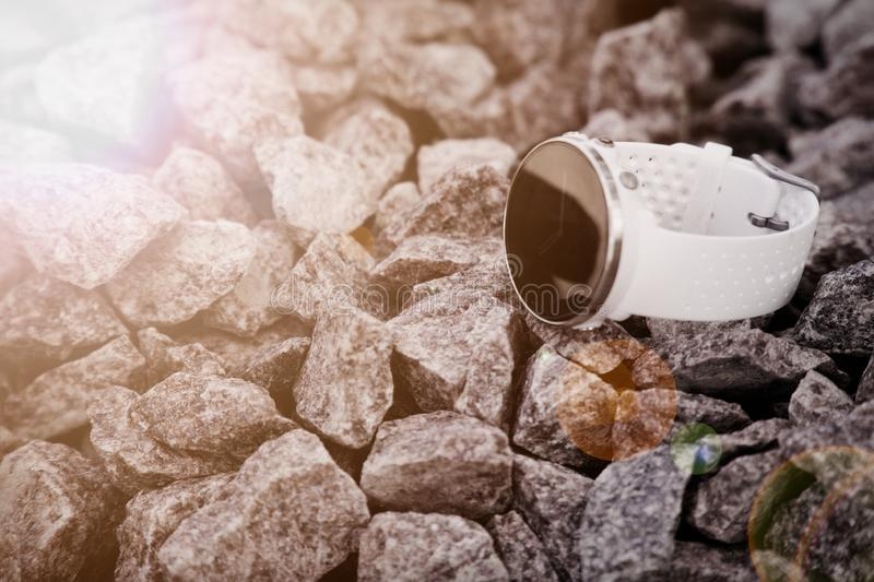 Sport watch for triathlon on the granite gravel. Smart watch for tracking daily activity and strength training. Sun beam lights stock photo
