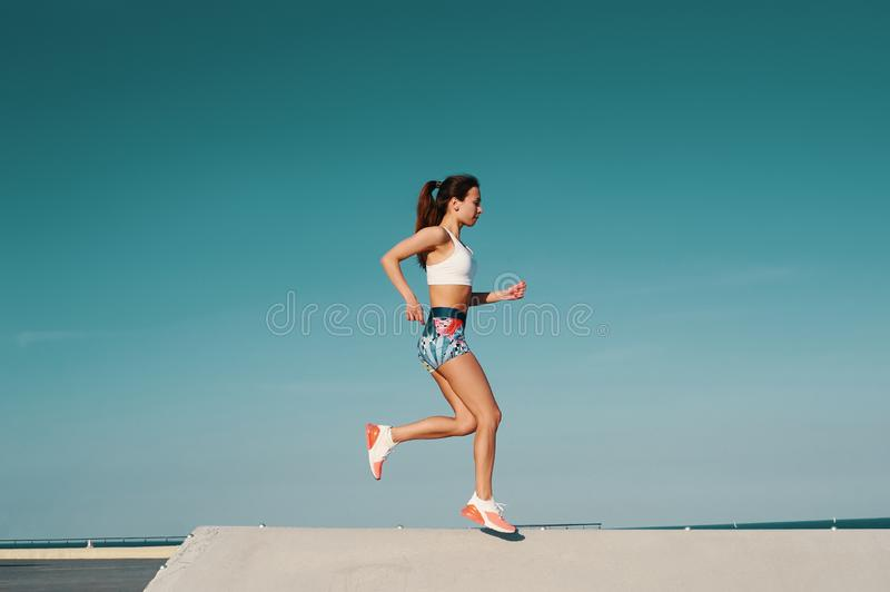 Sport is the way of her life. Full length of beautiful young woman in sports clothing jogging while exercising outdoors stock image