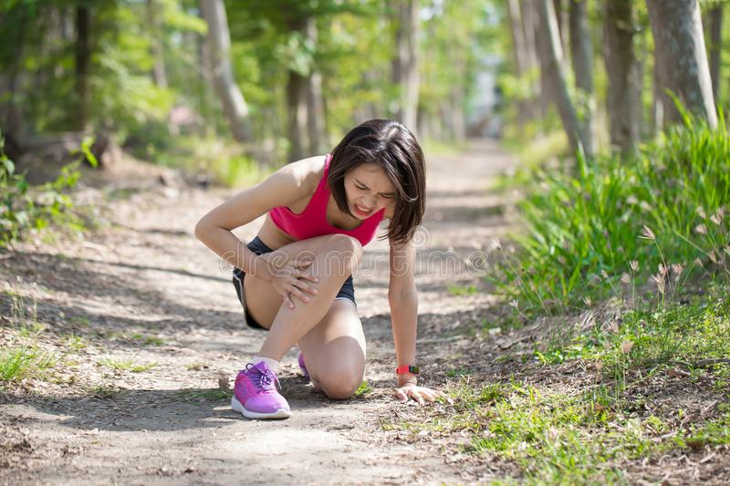 Sport woman with calf strain. Sport woman feel pain with calf strain in the forest stock photography