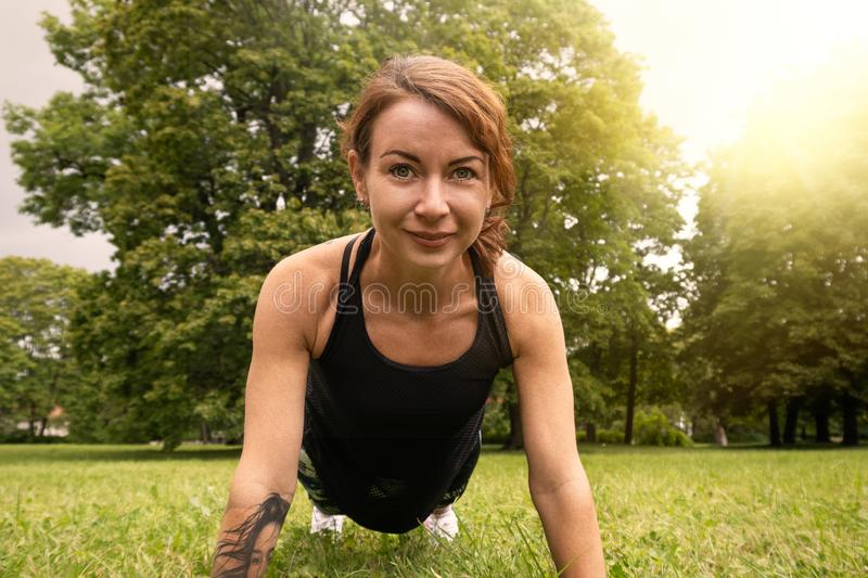 Sport woman doing fitness push up in park. Push ups or press ups exercise by young woman, working out on grass in park royalty free stock images