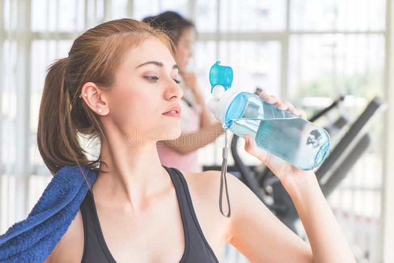 Sport Woman drinking fresh water in fitness gym royalty free stock image