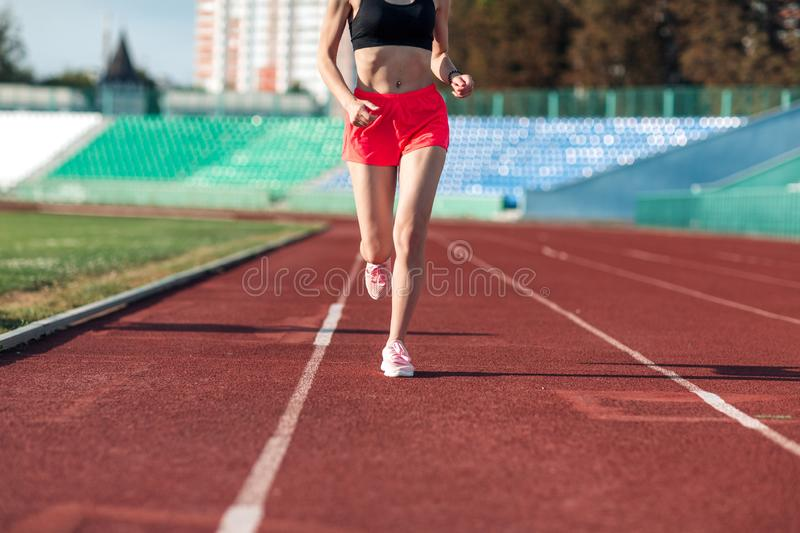 Sport. Woman fitness legs running on stadium. Close up of feet of a runner. Woman fitness jog workout wellness concept. Athlete. Runner feet running on running stock photography