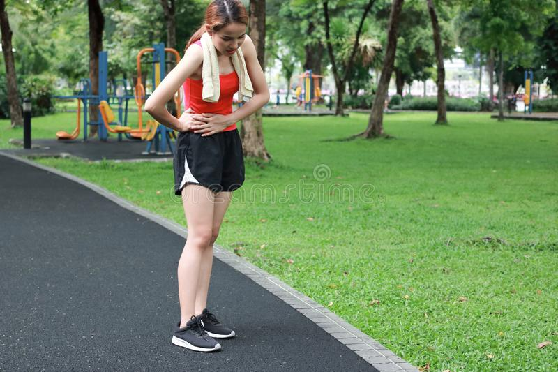 Sport woman having stomach pain during run in the park.  royalty free stock photography