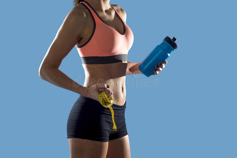 Sport woman holding water bottle and measure tape showing slim perfect abs and stomach royalty free stock photos