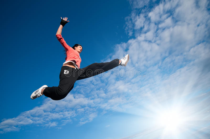 Sport woman jumping and fly over sky and sun. Beautiful sport woman in urban sportswear jumping and fly over blue sky with clouds and sun beam stock images