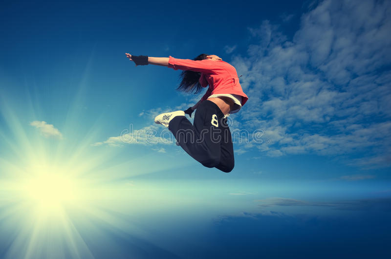 Sport woman jumping and fly over sky and sun. Beautiful sport woman in urban sportswear jumping and fly over blue sky with clouds and sun beam royalty free stock images