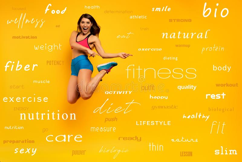 Sport woman jumps on a yellow background with most important fitness terms. Happy and joyful expression. Determinated sport woman jumps on a yellow background stock photo