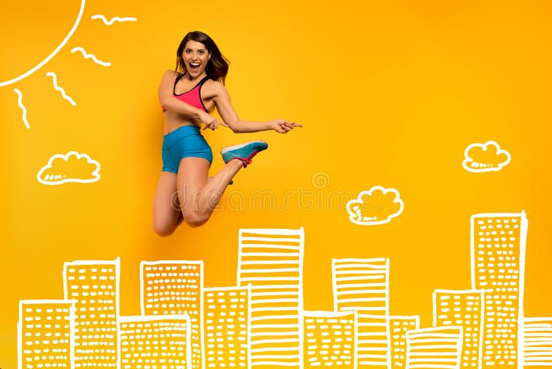 Sport woman jumps on a yellow background with Skyscrapers drawing. Happy and joyful expression. Determinated sport woman jumps on a yellow background with stock photo
