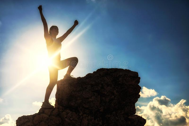 Sport woman raise hands at mountain summit. Silhouette sport hiking woman raise victory hands and stand on top of hill during sunset after climbing to mountain stock photos