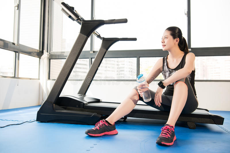 Sport woman rest on treadmill use smartwatch drinking water. Sport woman take rest on treadmill use smartwatch drinking water. indoors gym background. health stock photography