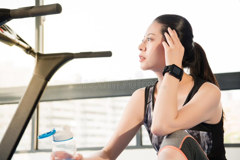 Sport woman rest on treadmill use smartwatch drinking water. Sport woman take rest on treadmill use smartwatch drinking water. indoors gym background. health stock images