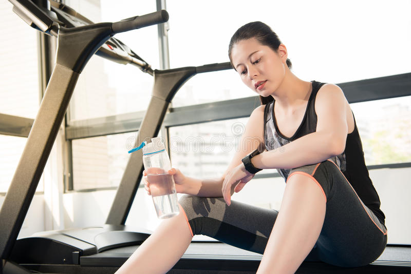 Sport woman rest on treadmill use smartwatch drinking water. Sport woman take rest on treadmill use smartwatch drinking water. indoors gym background. health royalty free stock images