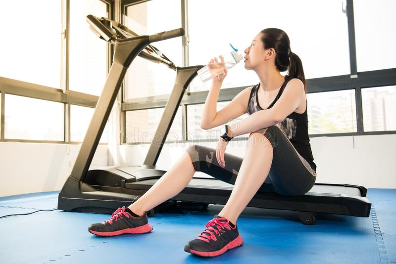 Sport woman rest on treadmill use smartwatch drinking water. Sport woman take rest on treadmill use smartwatch drinking water. indoors gym background. health royalty free stock photography