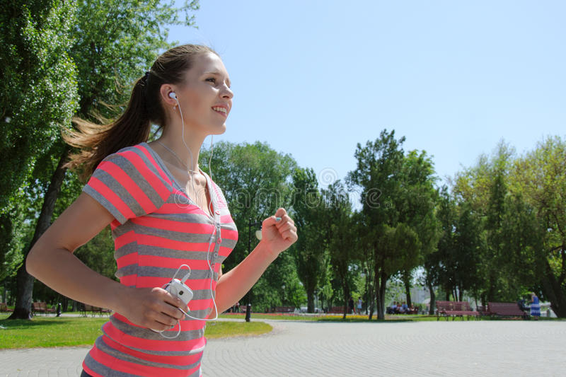 Sport woman running and listening to music stock photography