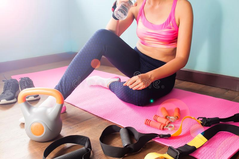 Sport woman sitting on pink color yoga mat with sport and fitness equipments on floor, Healthcare and beauty concept stock photos