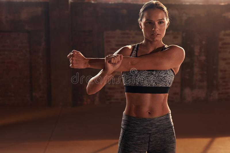 Sport woman stretching arms before fitness workout at gym royalty free stock photography