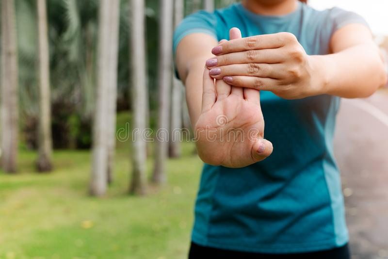 Sport woman stretching forearm before exercising. outdoor sport and excercise activities concept stock image