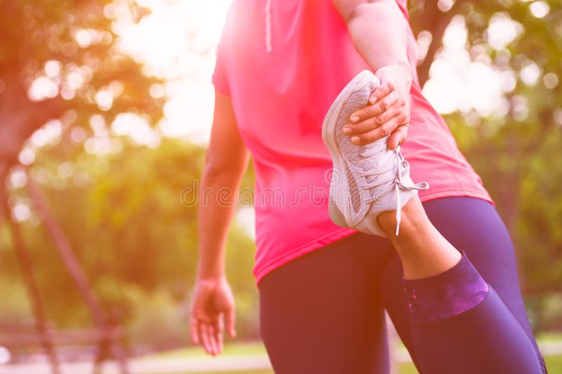 Sport woman stretching leg muscle preparing for running in the public park outdoor. Close up of female athlete lower body doing royalty free stock photos