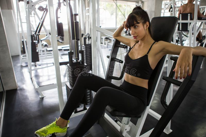 Sport woman taking a break after exercises on bench in gym.Tired Young fitness girl sitting rest workout  . relaxation. Relaxing, lifestyle, healthy, trainer royalty free stock images