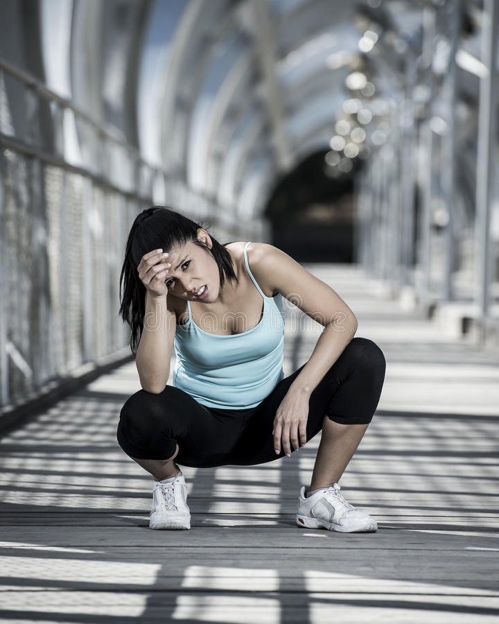 Sport woman tired and exhausted breathing and cooling down after running. Young beautiful and athletic sport woman tired and exhausted breathing and cooling down royalty free stock images