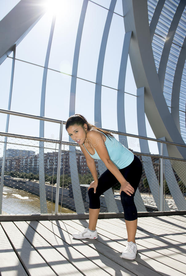 Sport woman tired and exhausted breathing and cooling down after running. Young beautiful and athletic sport woman tired and exhausted breathing and cooling down stock photos