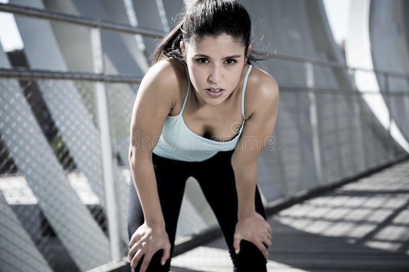 Sport woman tired and exhausted breathing and cooling down after running. Young beautiful and athletic sport woman tired and exhausted breathing and cooling down royalty free stock photos