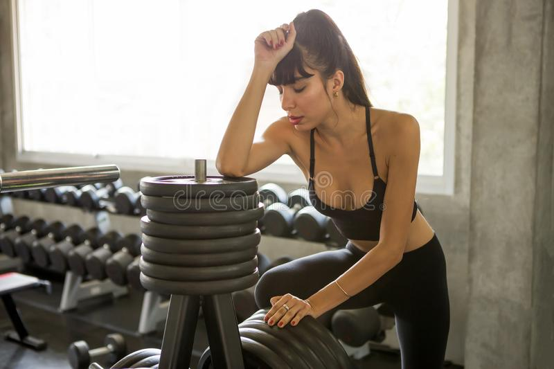 Sport woman tired taking a break from  weight lifting or exercise rest on Heavy weight plate machine and dumbbells shelf. Background  in fitness gym . healthy stock photos