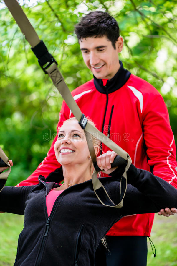 Sport woman with trainer at sling training royalty free stock photos
