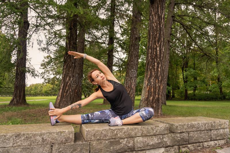 Sport womsport woman wearing exercise suit doing stretching fitness exercise in park royalty free stock images