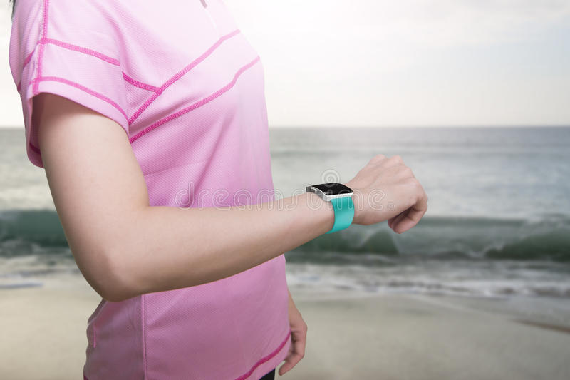Sport woman wearing smartwatch with blank black glass bent touch. Screen on natural sea beach background royalty free stock photos