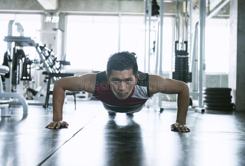 Sport. Young asian athletic man doing push-up muscular exercising in fitness gym.  stock images