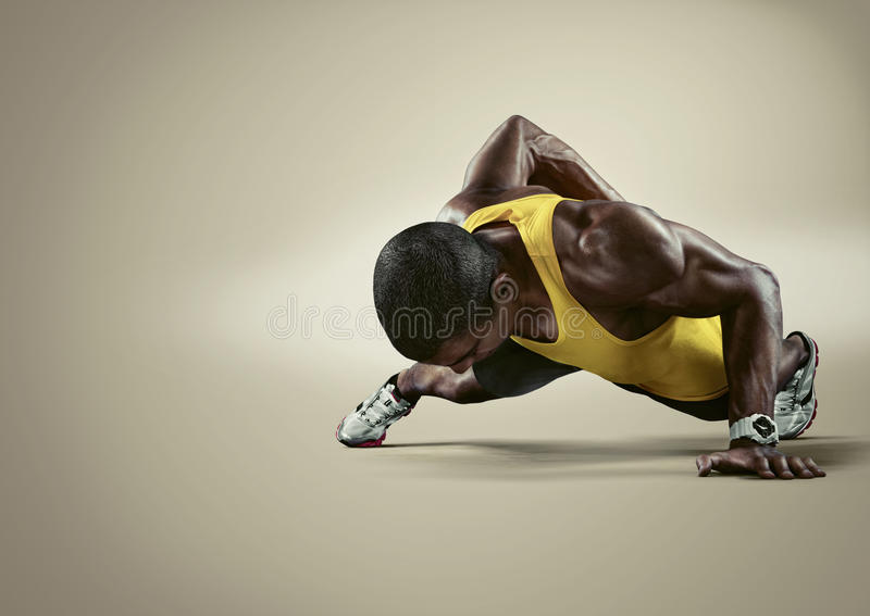 Sport. Young athletic man doing push-ups stock images