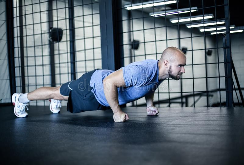 Sport. Young athletic man doing push-ups. Muscular and strong guy exercising. dressed in a sports uniform. Sport. Young athletic man doing push-ups. Muscular and royalty free stock photography
