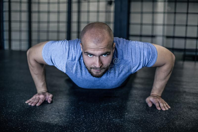 Sport. Young athletic man doing push-ups. Muscular and strong guy exercising. dressed in a sports uniform. Sport. Young athletic man doing push-ups. Muscular and stock images