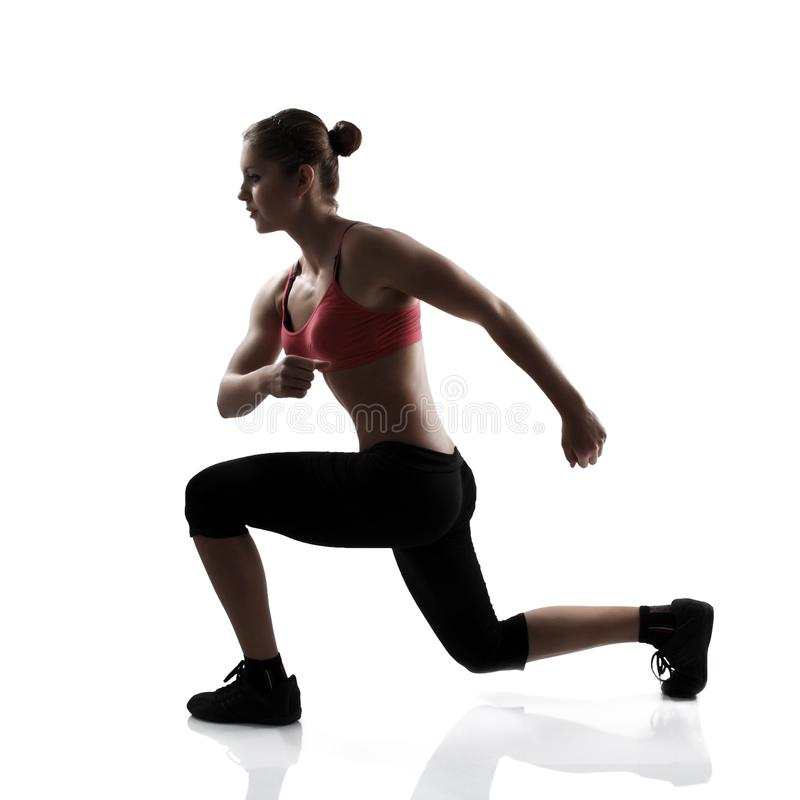 Sport young athletic woman doing lunge, silhouette studio shot o. Ver white background royalty free stock photos
