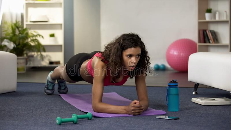 Sport young female doing plank exercise, mobile watch counting down time fitness stock images