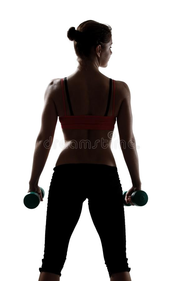 Sport young woman with dumbbells, back view, silhouette studio s. Hot over white background stock images