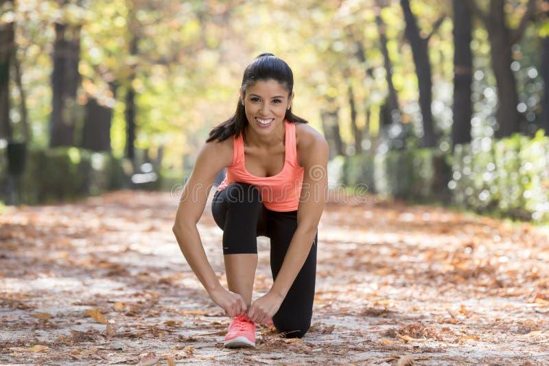 Sporta biegacza kobieta wiąże jej obuwiane tenisówka koronki uśmiecha się szczęśliwego przygotowywającego dla biega i jogging tre zdjęcia royalty free