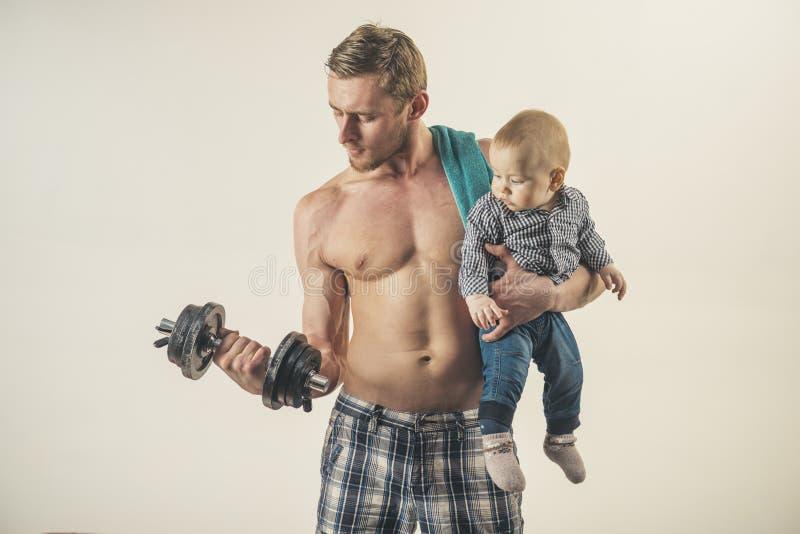 sporta czas Ojciec budowy bicepsów triceps z synem rodzinny zdrowy styl życia Silny mężczyzna z dumbbells chwyta chłopiec fotografia royalty free