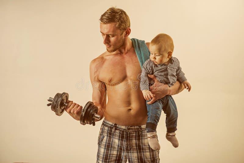sporta czas Ojciec budowy bicepsów triceps z synem rodzinny zdrowy styl życia Silny mężczyzna z dumbbells chwyta chłopiec fotografia stock