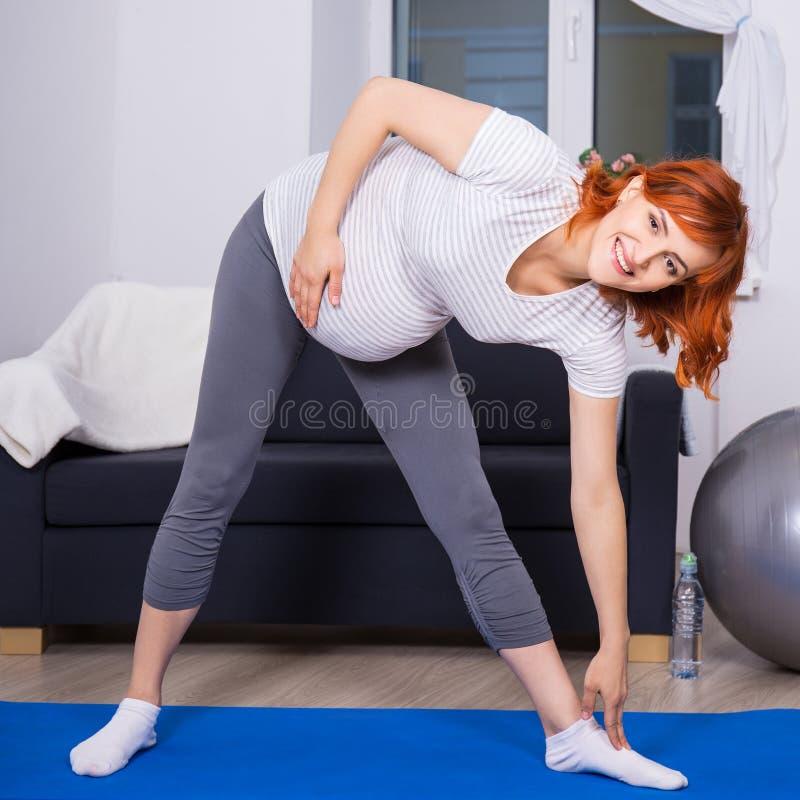 Sporta i brzemienności pojęcie - kobieta w ciąży robi rozciągać ex zdjęcie royalty free
