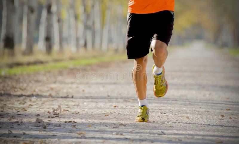 Sporta mężczyzna biega outdoors w drogowym śladzie z gruntuje w sprawności fizycznej i zdrowym stylu życia pojęciu fotografia royalty free