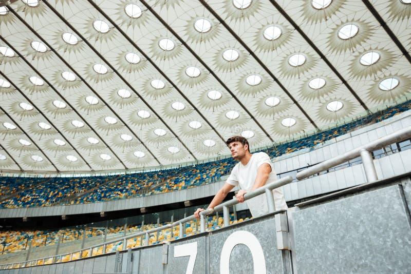 Sporta mężczyzna pozycja przy stadium outdoors i patrzejący na boku obrazy stock