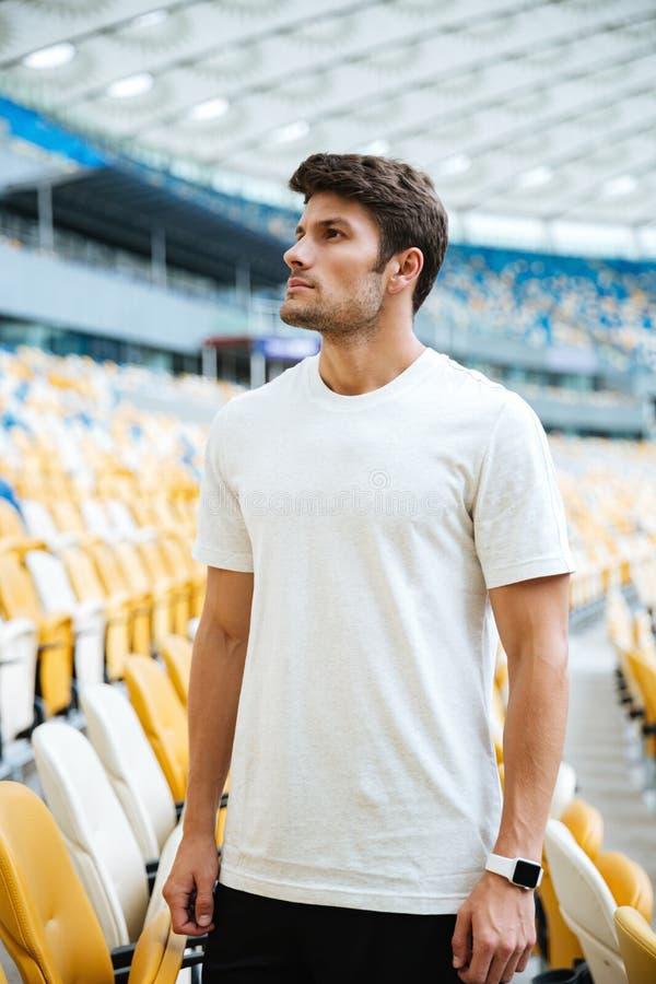 Sporta mężczyzna pozycja przy stadium outdoors i patrzejący na boku fotografia royalty free